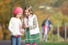 Two Young Girl Listening To MP3 Player Outdoors Royalty Free Stock Image