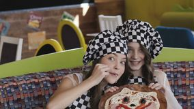 Two young girl with smile presentating a pizza for camera. Slowly stock video