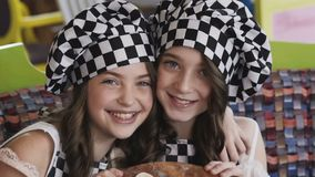 Two young girl with smile presentating a pizza for camera. Slowly stock video footage