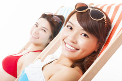 Two young girl sunbathing and lying on a beach chair Royalty Free Stock Photo