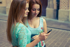 Two young girl using GPS in mobile phone. Urban backbround. Royalty Free Stock Photos