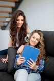 Two young girl watching the tablet at home Royalty Free Stock Photos