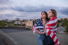 Two young girl wrapped in american flag Royalty Free Stock Photos