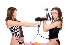 Two young girlfriends with hair dryers Royalty Free Stock Photos