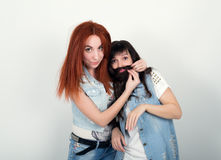 Two young girlfriends indulge and grimace, make each other a mustache out of the hair. Teenager making moustache from Stock Photo