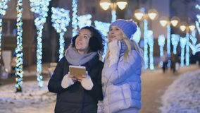 Two young girlfriends looks with surprise at winter evening city. Two young girls stands outdoors with tablet. Cute girls are surprised to see the winter night stock video