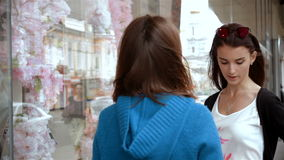 Two young girlfriends met on the streets. And chatting near the store stock video footage