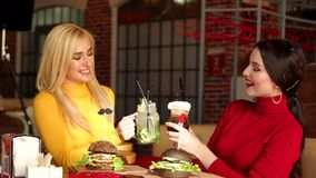 Two young girlfriends rest in a cafe, they clink bright cocktails. stock footage