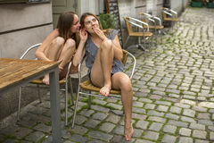 Two young  girlfriends sitting at the table of outdoors cafe and whispering. Royalty Free Stock Images