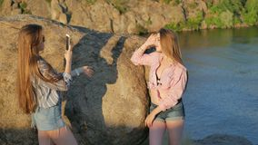 Two young girlfriends with a smartphone on the rock. Are photographed stock footage
