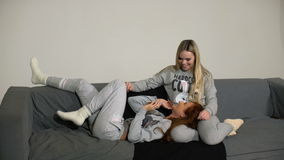 Two young girlfriends with smartphone on sofa in home. Two young girlfriends with smartphone on sofa on a white background stock video footage