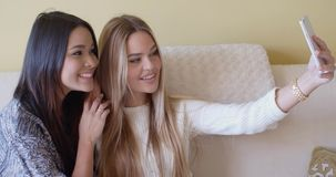 Two young girlfriends taking a selfie at home. Two young girlfriends taking a selfie on a mobile phone at home as they relax together on a sofa posing and stock footage