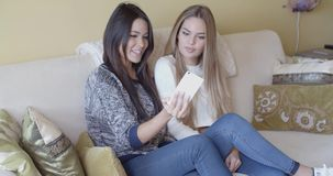 Two young girlfriends taking a selfie at home. Two young girlfriends taking a selfie on a mobile phone at home as they relax together on a sofa posing and stock video