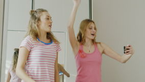 Two young girlfriends teens learn to dance funny dance. Take a look at the mobile phone screen and repeat the movement. Pjm party stock video footage