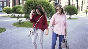Two young girlfriends walking in a summer street with coffee cups. Two attractive young girlfriends are walking in a summer street with coffee cups and holding stock video footage