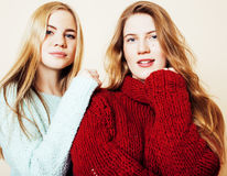 Two young girlfriends in winter sweaters indoors having fun. Lif Stock Photo