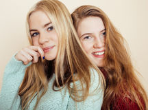 Two young girlfriends in winter sweaters indoors having fun. Lifestyle. Blond teen friends close up. Smiling Stock Images