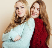 Two young girlfriends in winter sweaters indoors having fun. Lifestyle. Blond teen friends close up. Smiling Royalty Free Stock Photo
