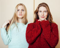 Two young girlfriends in winter sweaters indoors having fun. Lifestyle. Blond teen friends close up Royalty Free Stock Image