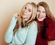 Two young girlfriends in winter sweaters indoors having fun. Lifestyle. Blond teen friends close up Stock Photography