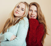 Two young girlfriends in winter sweaters indoors having fun. Lifestyle. Blond teen friends close up. Smiling Stock Image