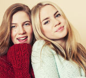 Two young girlfriends in winter sweaters indoors having fun. Lifestyle. Blond teen friends close up. Smiling Royalty Free Stock Image