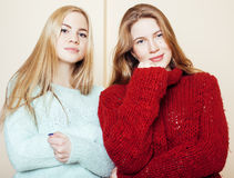 Two young girlfriends in winter sweaters indoors having fun. Lifestyle. Blond teen friends close up. Smiling Stock Photos