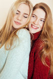 Two young girlfriends in winter sweaters indoors having fun. Lifestyle. Blond teen friends close up Royalty Free Stock Photography