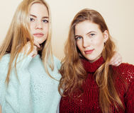 Two young girlfriends in winter sweaters indoors having fun. Lifestyle. Blond teen friends close up Stock Photos