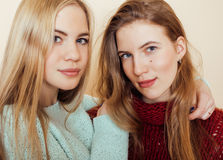 Two young girlfriends in winter sweaters indoors having fun. Lifestyle. Blond teen friends close up Stock Image