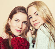 Two young girlfriends in winter sweaters indoors having fun. Lifestyle. Blond teen friends close up Stock Photo