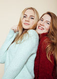 Two young girlfriends in winter sweaters indoors having fun. Lifestyle. Blond teen friends close up. Smiling Royalty Free Stock Images