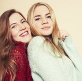 Two young girlfriends in winter sweaters indoors having fun. Lifestyle. Blond teen friends close up Royalty Free Stock Photos