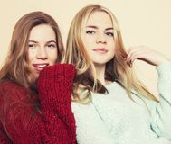 Two young girlfriends in winter sweaters indoors having fun. Lifestyle. Blond teen friends close up. Smiling Stock Photo
