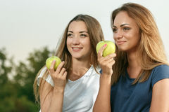 Two young girls with apples in the park. Two young beautiful girls with apples in the park Royalty Free Stock Images