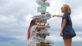 Two young girls argue and choosing which way they should go. wooden sign post arrows pointing to various cities and stock video