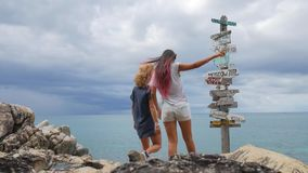 Two young girls argue and choosing which way they should go. wooden sign post arrows pointing to various cities and stock footage