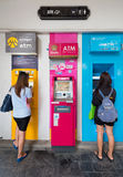Two young girls at ATM in Thailand Royalty Free Stock Photography