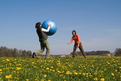 Two young girls with ball. Two young girls playing with big ball on the spring meadow Stock Photography