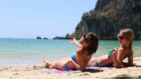 Two young girls beckon somebody with gestures. Young brunette and blonde girls beckon somebody with gestures sitting on sand beach against cliff stock video footage