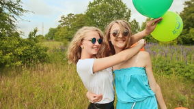 Two young girls are best friends cuddling with balloons. Two teen girl friends having fun together with colorful balloons. Photo toned style Instagram filters stock video