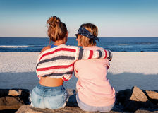 Two young girls, best friends sitting together on the beach at s. Unset. Friendship, happiness, beach, summer concept Royalty Free Stock Photo