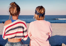 Two young girls, best friends sitting together on the beach at s. Unset. Friendship, happiness, beach, summer concept Stock Photography