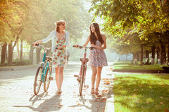 The two young girls with bicycles in park Royalty Free Stock Photography