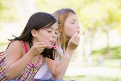 Two young girls blowing bubbles Royalty Free Stock Images