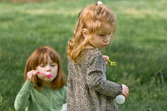 Two young girls blowing bubbles. And having fun on a early spring afternoon Stock Images