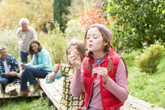 Two Young Girls Blowing Bubbles Outside Stock Photo