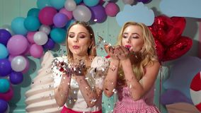 Two young girls blowing on confetti or tinsel on bright colorful background. Two charming beautiful young girls blowing on confetti or tinsel on bright colorful stock video