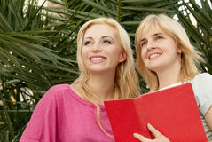 Two young girls with the book Stock Images