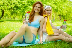 Two young girls with bottles of water on grass Stock Photography